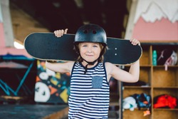 Portrait of handsome caucasian boy athlete skateboarder in protective helmet with skateboard in hands looking at camera on background of skate park. A child and an active hobby, sports and health.