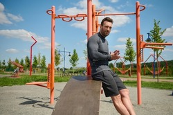 Portrait of handsome Caucasian macho, attractive sporty man, European muscular build athlete looking at the camera on the background of cross bars and gym machines in summer outdoor sportsground