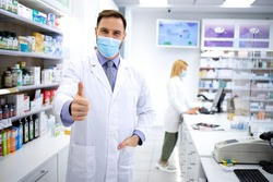 Portrait of handsome caucasian male pharmacist with face mask standing in pharmacy store.