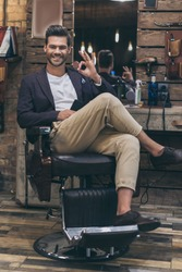 Portrait of handsome caucasian man with fashionable hairstyle at barber shop