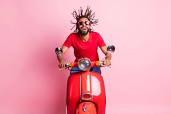 Portrait of handsome cheery dreamy guy riding moped having fun wind blowing spending summer isolated over pink pastel color background