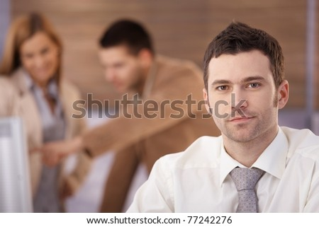 Portrait of handsome confident businessman sitting in office, colleagues talking in background.?