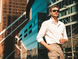 Portrait of handsome confident stylish hipster lambersexual model.Modern man dressed in white shirt. Fashion male posing in the street background near skyscrapers in sunglasses. Outdoors at sunset