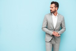 Portrait of handsome confident stylish hipster lambersexual model.Sexy modern man dressed in elegant suit. Fashion male posing in studio near blue wall.