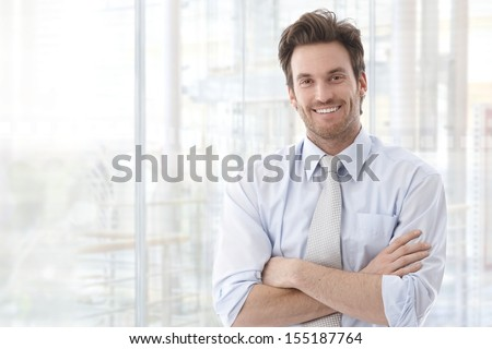 Portrait of handsome confident young businessman standing arms crossed, smiling happy, looking at camera.