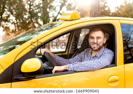 Portrait of handsome driver in taxi car