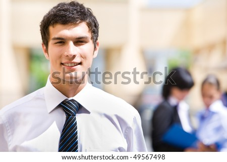 Portrait of handsome employer looking at camera with smile in working environment