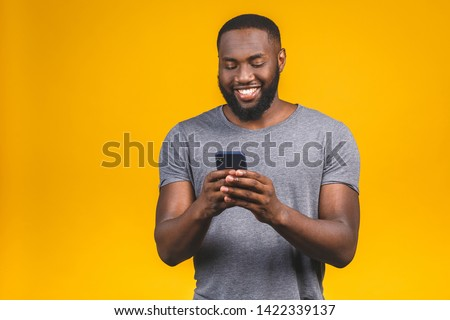 Portrait of handsome excited cheerful joyful delightful curious guy wearing casual sending and getting messages to his lover isolated against yellow background. Using phone.
