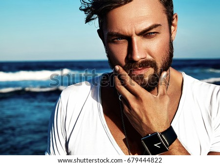Portrait of handsome fashion man model wearing white clothes posing on blue sea background. Touching his beard #679444822