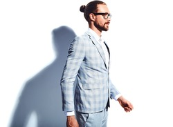 portrait of handsome fashion stylish hipster businessman model dressed in elegant light blue suit in glasses isolated on white. Walking