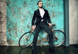 portrait of handsome fashion stylish hipster lumbersexual businessman model dressed in elegant black suit posing near sport bicycle and blue grange wall in studio. Metrosexual