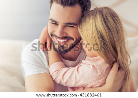 Portrait of handsome father and his cute daughter hugging and smiling