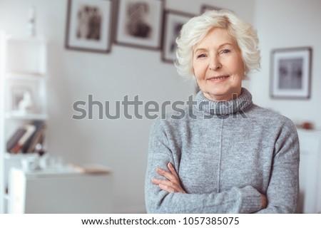 Portrait of handsome grandmother in gray sweater, crossed hands