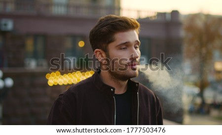 Portrait of handsome guy blowing smoke from e-cigarette outdoors. Closeup hipster man smoking electronic cigarette in urban background. Attractive male person vaping outside.
