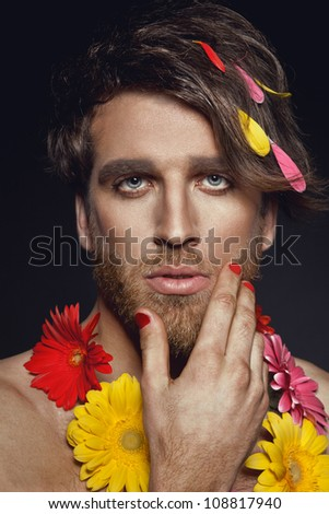 Portrait of handsome guy with gerbera flowers and red nails
