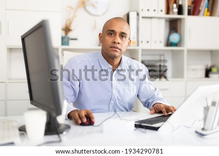 Portrait of handsome hispanic employee looking at camera and sitting at office desk Stock photo ©