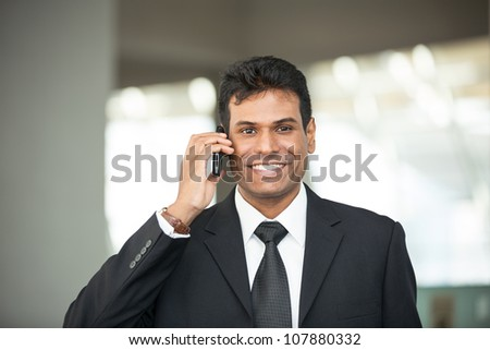 Portrait of handsome Indian business man using cell phone.