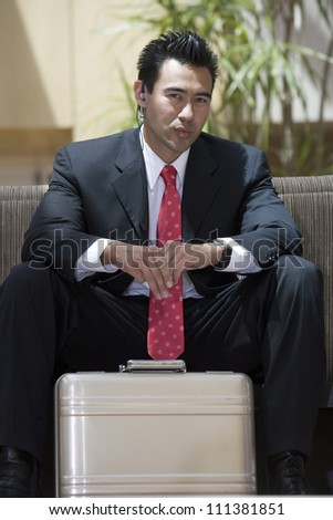 Portrait of handsome Japanese businessman with suitcase