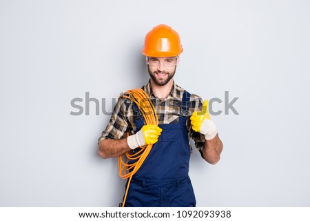 Portrait of handsome joyful electrician in hardhat, overall, shirt with bristle, holding rolled wires on shoulder, showing thumb up recommend approve sign over grey background #1092093938