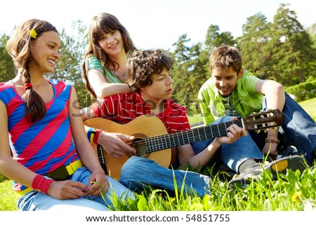 Portrait of handsome lad playing the guitar surrounded by his friends