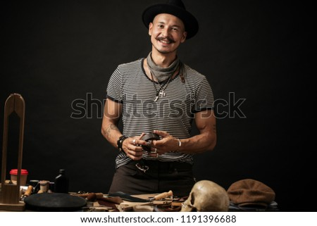 Portrait of handsome Leather goods craftsman in stylish hat doing handbags and leather accessories for ladies in his workshop on black dark background. Small business concept photo. Foto d'archivio ©
