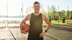Portrait of handsome male basketball player smiling at camera while posing with a basketball on the court on a sunny day. Sport, active lifestyle concept. Front view. Web Banner