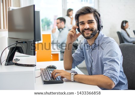 Portrait of handsome male customer service representative, call centre worker, agent, operator, support staff speaking with head set in modern office.