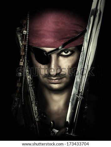 Portrait of handsome male pirate holding sword on black background