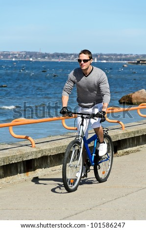 Portrait of handsome male riding a bicycle by the sea
