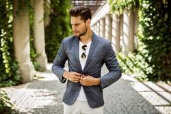 Portrait of handsome man buttoning jacket