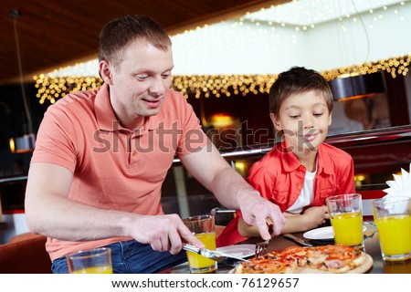 Portrait of handsome man cutting pizza with his son near by in pizzeria
