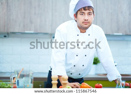 Portrait of handsome man in cook uniform looking at camera