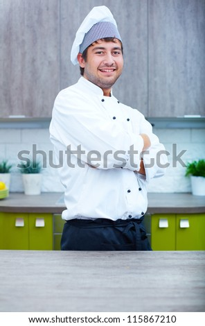 Portrait of handsome man in cook uniform looking at camera in the kitchen - stock photo