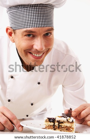 Portrait of handsome man in cook uniform looking at camera with tasty piece of cake near by