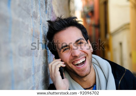Portrait of handsome man in urban background talking on phone and laughing