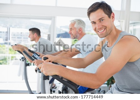 Portrait of handsome man on exercise bike in fitness club