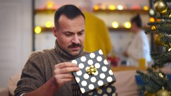 Portrait of handsome man opening christmas present and feeling disappointed. Guy standing near christmas tree unpacking gift and looking unhappy