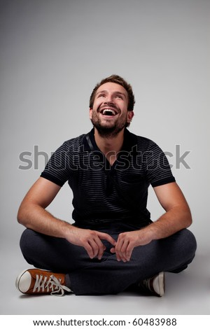 Portrait of handsome man sitting with crossed legs
