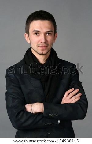 Portrait of  handsome man standing on gray background.