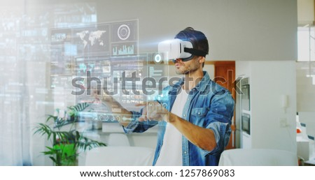 Portrait of handsome man using vr glasses with futuristic augmented reality holograph in living room. Concept of innovation technology, lifestyle, entertainment.