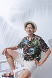 Portrait of handsome man w casual Summer wearing new stylish floral ,palm pattern T-shirts ,hat with white shorts sitting chair palm shadow