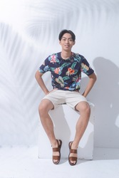 Portrait of handsome man w casual Summer wearing new stylish floral ,palm pattern T-shirts with white shorts sitting chair palm shadow