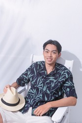 Portrait of handsome man w casual Summer wearing new stylish leaves pattern T-shirts ,hat with white shorts sitting chair palm shadow