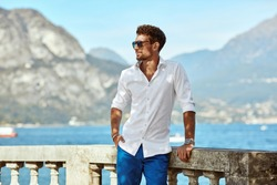 Portrait of handsome man wearing elegant white shirt and sunglasses, standing near the lake in the alps