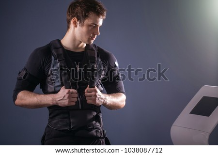 portrait of handsome man wearing ems suit near electro muscle stimulation machine #1038087712