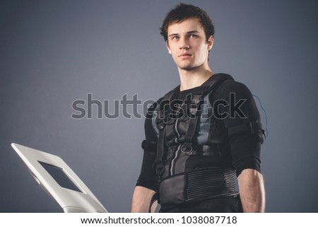 portrait of handsome man wearing ems suit near electro muscle stimulation machine #1038087718