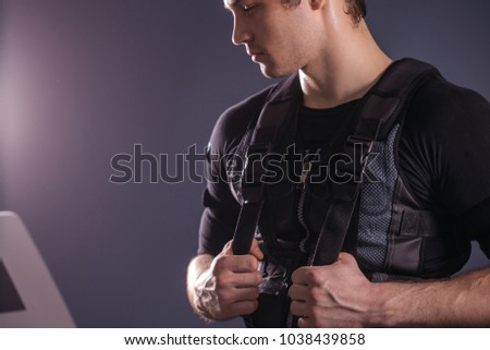 portrait of handsome man wearing ems suit near electro muscle stimulation machine #1038439858