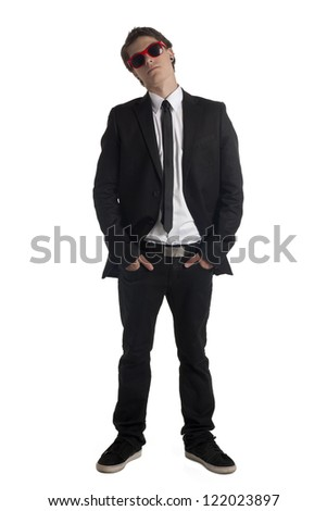 Portrait of handsome man wearing tuxedo and shades standing on a white surface