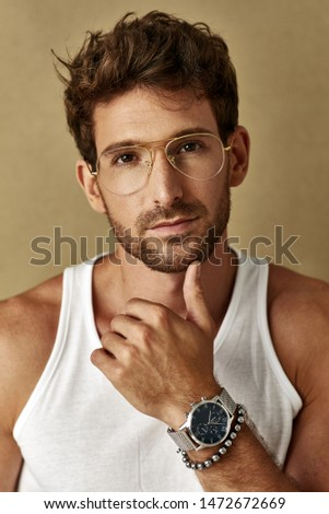 Portrait of handsome man with glasses on wearing watch