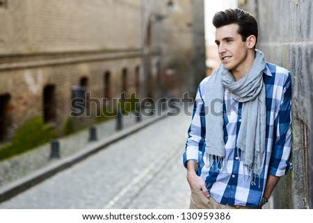 Portrait of handsome man with modern hairstyle smiling in urban background
